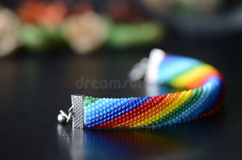 Den handgjorda virkade armbandregnbågen färgar på en mörk bakgrund royaltyfri foto