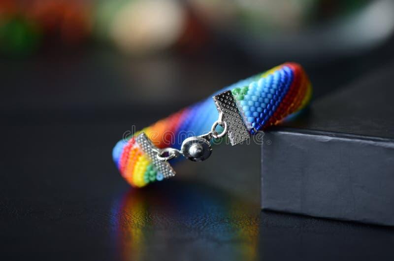 Den handgjorda virkade armbandregnbågen färgar på en mörk bakgrund arkivbild