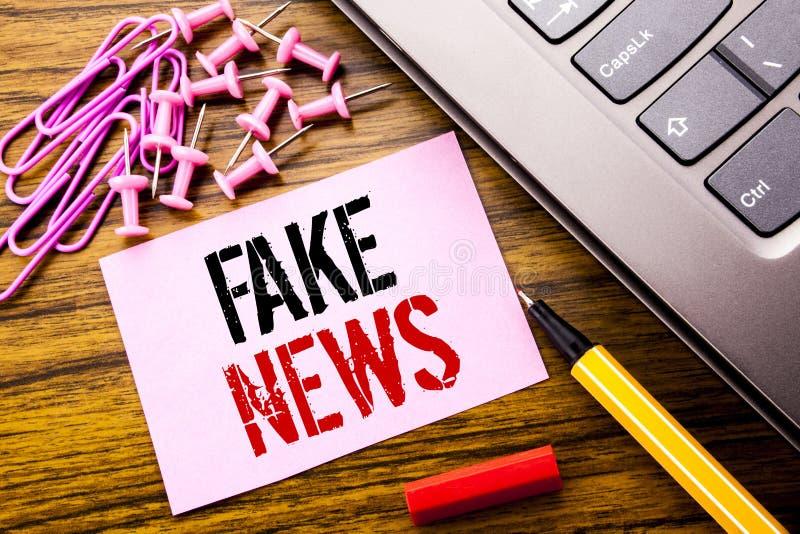 Den handskrivna textvisningen fejkar nyheterna Affärsidé för Hoax journalistik som är skriftlig på rosa klibbigt anmärkningspappe fotografering för bildbyråer