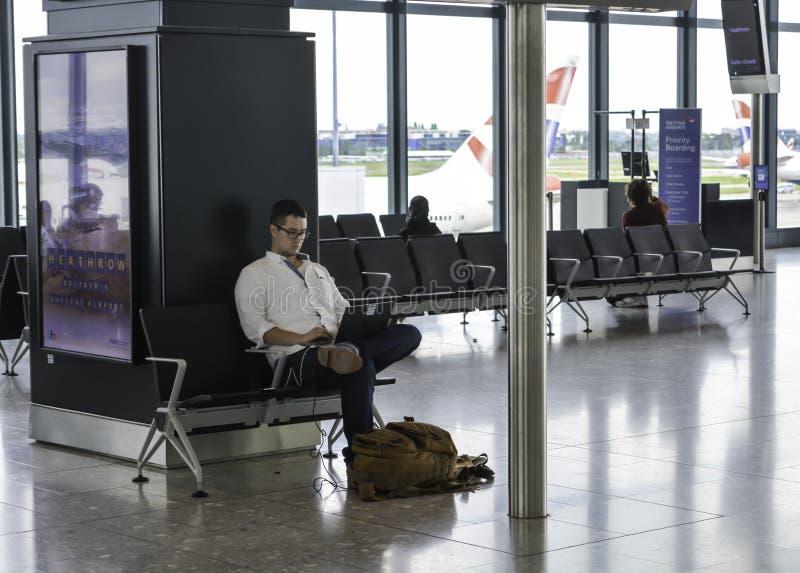 Den Heathrow flygplatsen - man arbete på hans bärbar dator arkivbilder