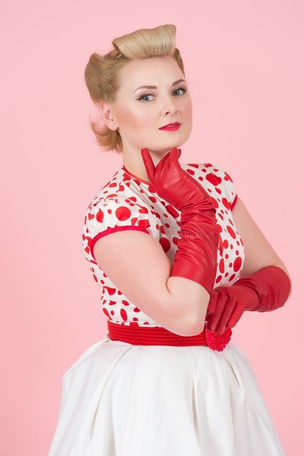 Den Heerful blondinen utformade unga flickan med hennes hand nära hakan och röda långa handskar på att se för bakgrund för pastel arkivfoton