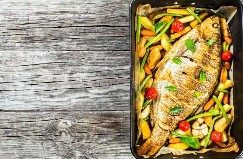 Den hela fisken bakade i en stekhet maträtt, bästa sikt arkivbild
