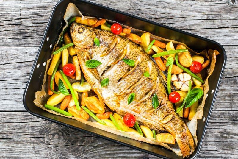 Den hela fisken bakade i en stekhet maträtt, bästa sikt arkivfoton