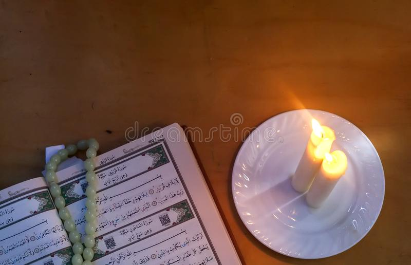 Den heliga quranen och ljusen Koranen f?r helig bok f?r muselmaner Öppna sidor av den heliga quranen fritt avst?nd arkivbild