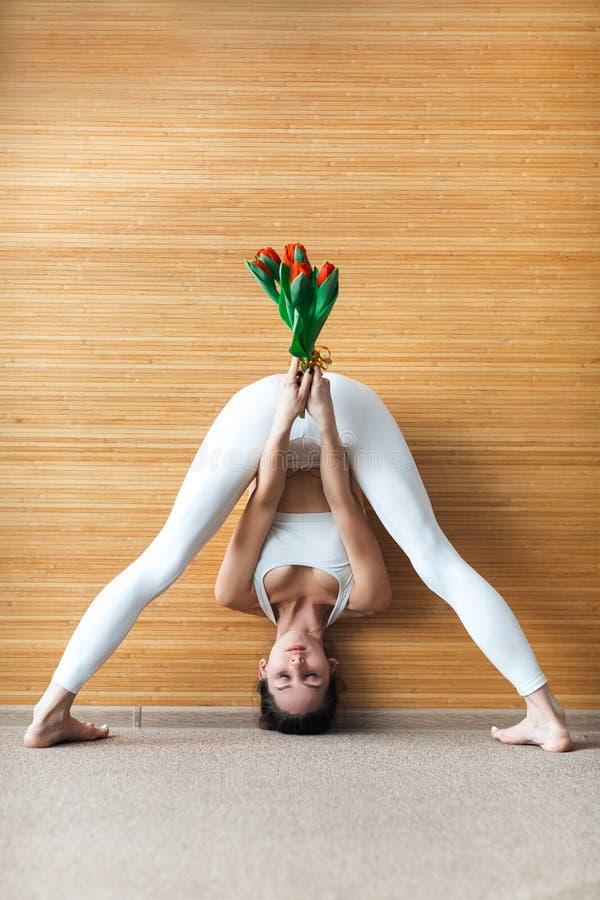 Den hellånga främre sikten av den sportiga unga kvinnan i en praktiserande yoga för vit dräkt som gör att stå, grenslar den framå royaltyfria foton