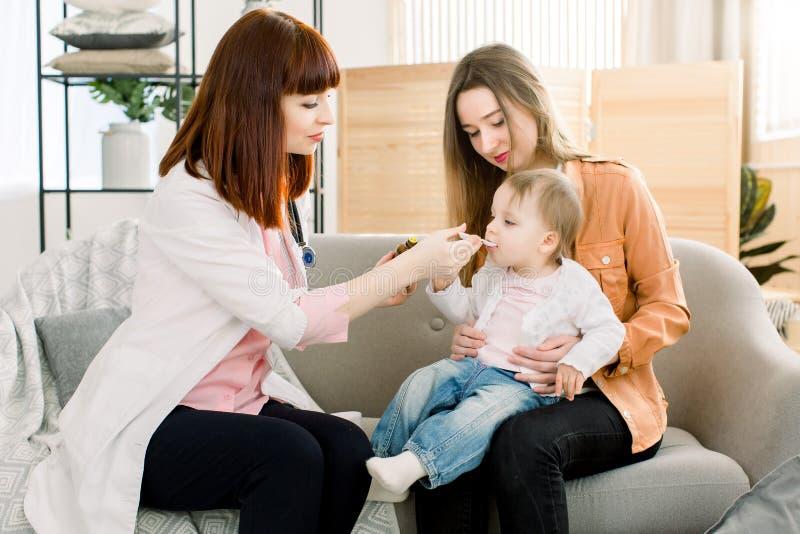 Den hem- kvinnadoktorn i det vita laget undersöker behandla som ett barn lite hemma eller i klinik Snälla läkareterapeutblickar g royaltyfria bilder