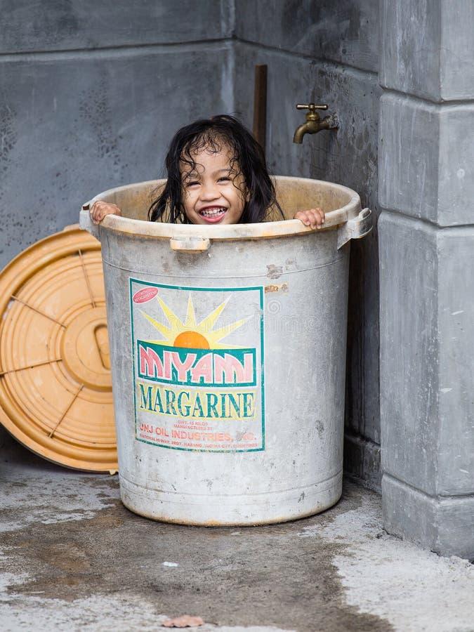 Den hemlösa flickan badar i en plast- hink, Filippinerna royaltyfria bilder