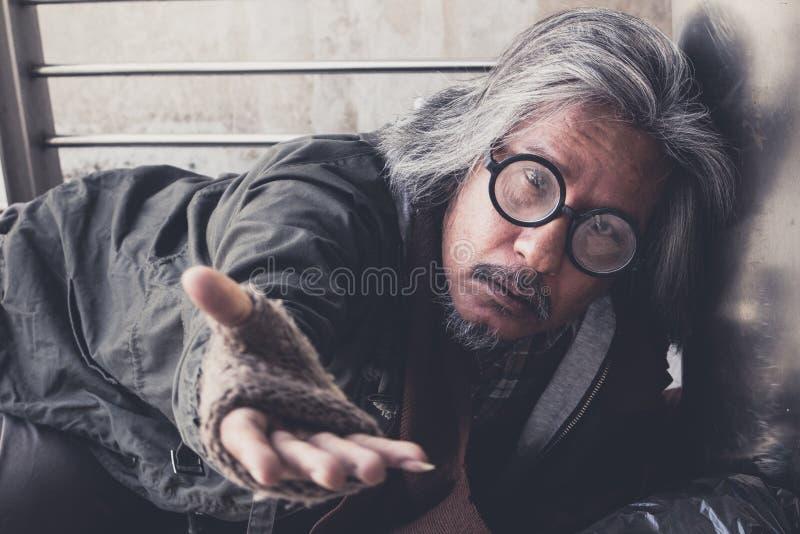 Den hemlösa hungriga mannen att visa honom för att räcka önskar pengar av mat på gångbanagatan i staden arkivfoton