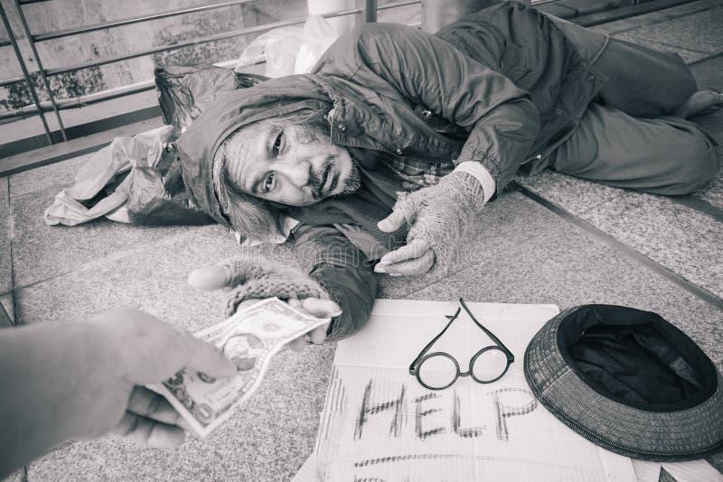 Den hemlösa hungriga mannen att visa honom för att räcka önskar att pengar på gångbanagatan i staden, vänlighetfolk ska ge honom royaltyfri bild