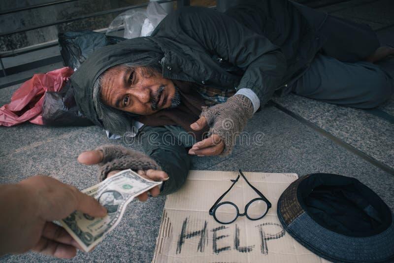 Den hemlösa hungriga mannen att visa honom för att räcka önskar att pengar på gångbanagatan i staden, vänlighetfolk ska ge honom fotografering för bildbyråer