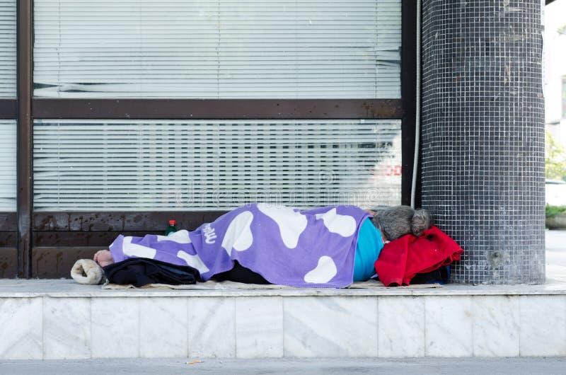Den hemlösa kvinnan sover på gatan arkivbild