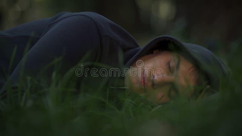 Den hemlösa mannen som sover på gräs parkerar in, armod och det sociala frågebegreppet royaltyfria foton