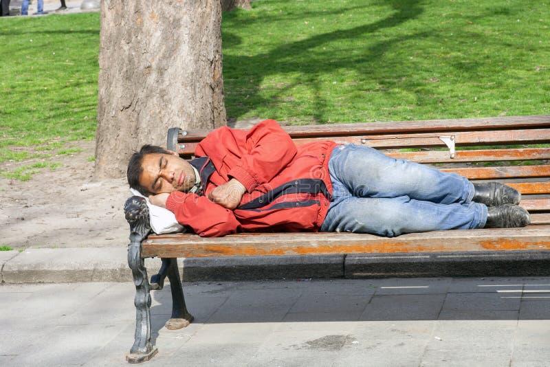 Den hemlösa mannen som sover på träbänk parkerar in royaltyfri foto