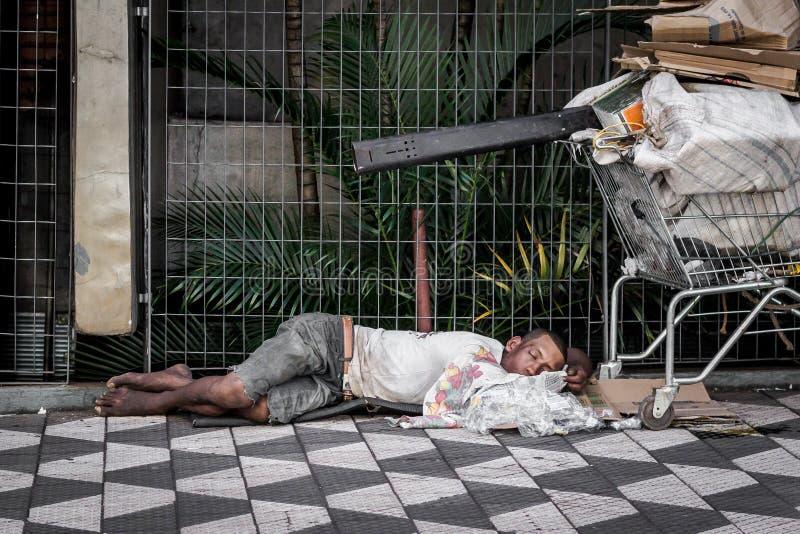 Den hemlösa mannen sover med en shoppingvagn royaltyfri foto