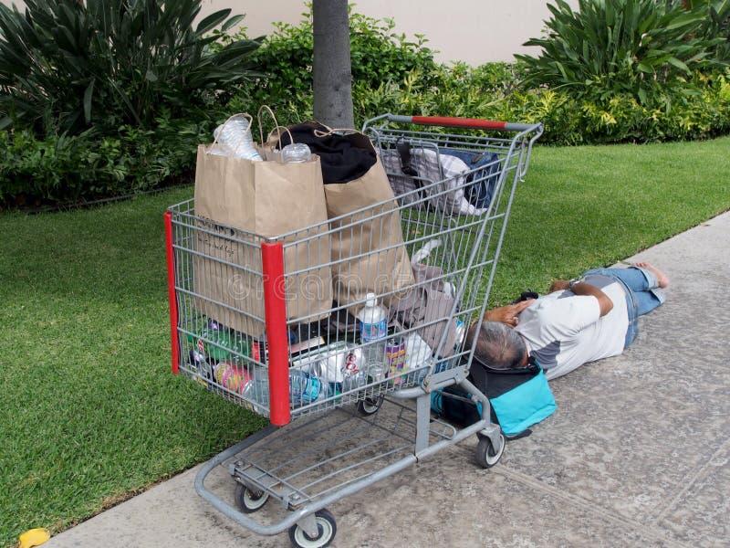 Den hemlösa mannen sover med huvudet som vilar på en påse på trottoaren royaltyfria foton