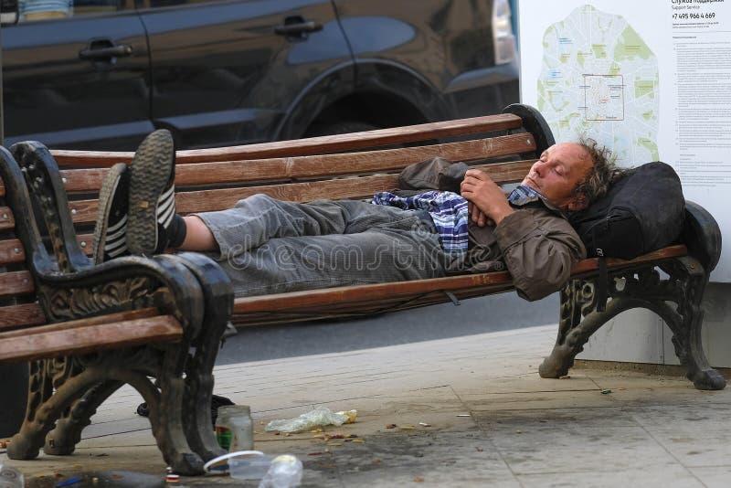 Den hemlösa mannen sover på en bänk arkivbilder