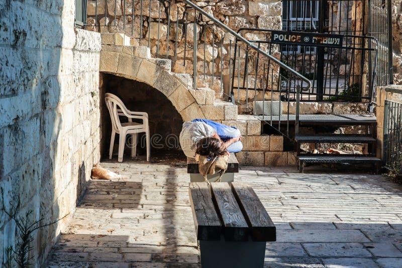 Den hemlösa mannen sover på en bänk på soluppgång i den judiska fjärdedelen i den gamla staden av Jerusalem royaltyfria foton