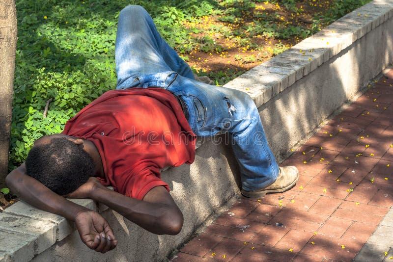 Den hemlösa mannen sover på fyrkanten royaltyfria foton