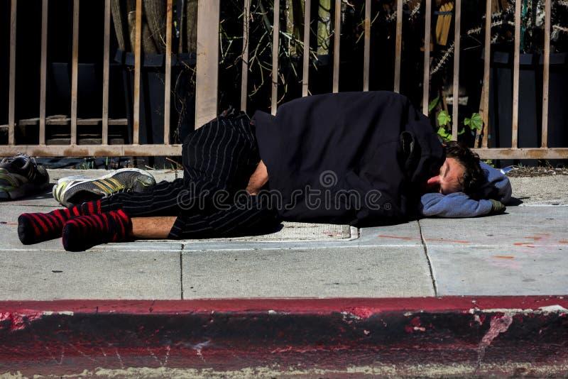 Den hemlösa mannen sover på gatorna av Hollywood, Los Angeles, CA royaltyfri foto