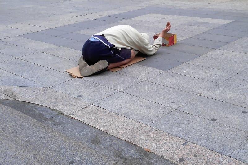 Den hemlösa mannen tigger för pengar arkivbilder