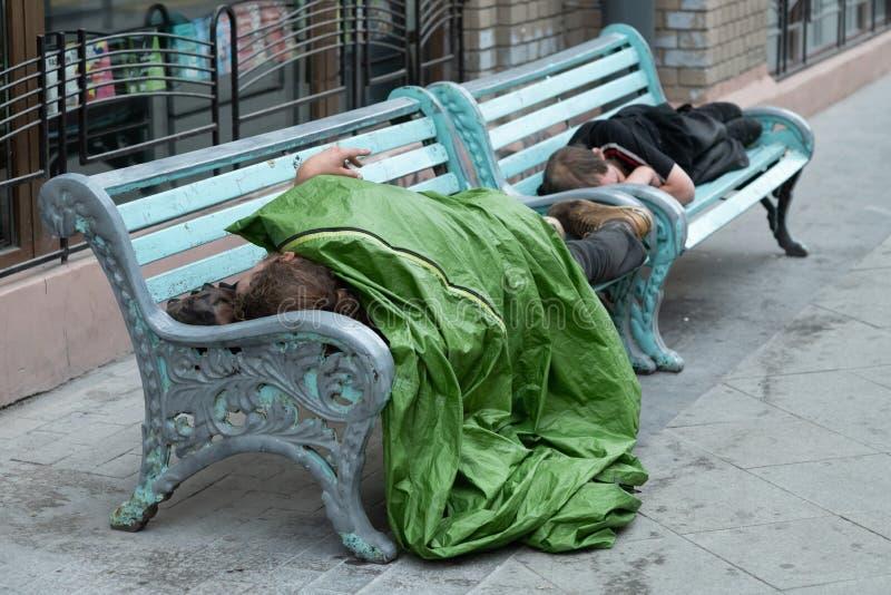Den hemlösa personen sover på en bänk i en kall höstdag i parkerar i europeisk union& x27; Bulgarien för mest fattig land för s arkivfoto