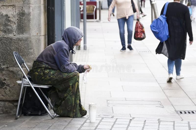 Den hemlösa tiggaren satt på den upptagna gatan som bär en hoodie med koppen för ändring i UK med shoppare i bakgrunden arkivbilder