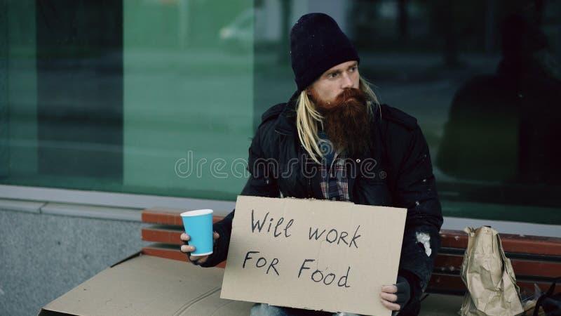 Den hemlösa unga mannen tigger för pengar som skakar koppen för att betala uppmärksamhetfolk som går nära tiggare på stadstrottoa royaltyfri foto