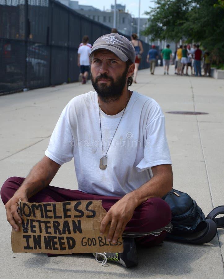 Den hemlösa veteran stoppar, som han tigger för pengar arkivbilder