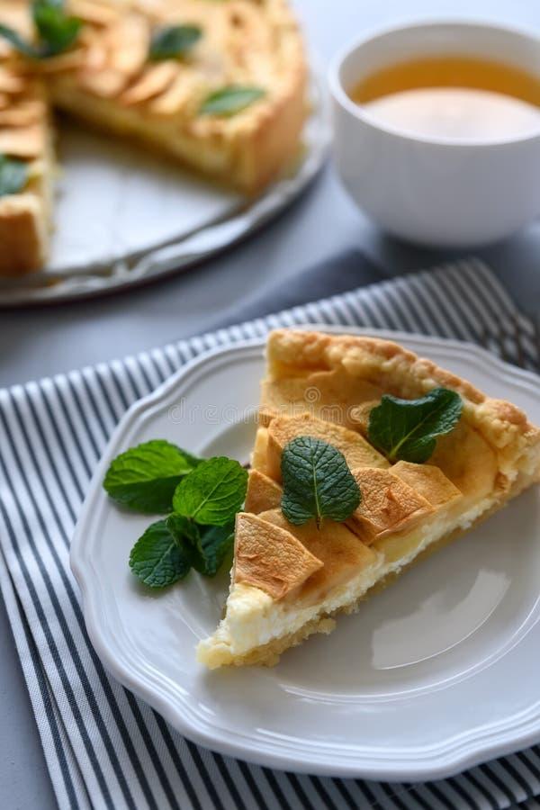 Den hemlagade äppelpajen med ost dekorerade mintkaramellsidor på grå träbakgrund Teatime eller vegetariskt matbegrepp selektivt arkivfoto