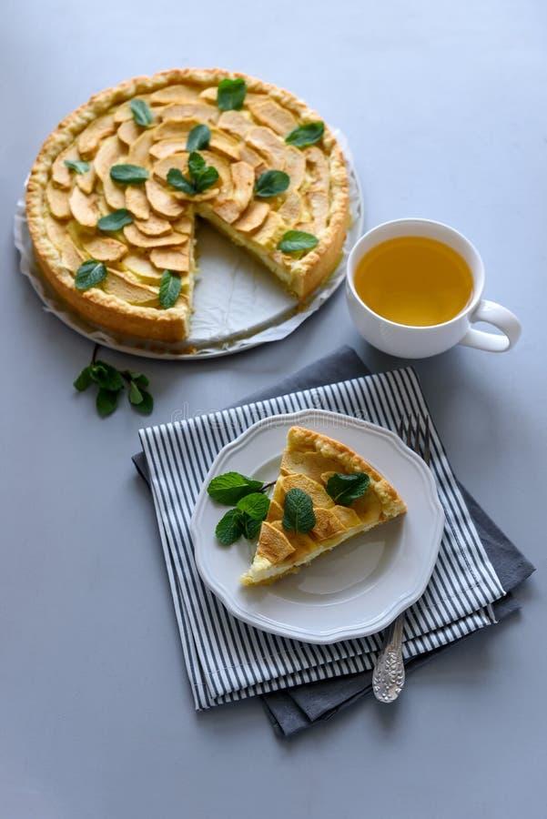 Den hemlagade äppelpajen med ost dekorerade mintkaramellsidor på grå träbakgrund Teatime eller vegetariskt matbegrepp selektivt arkivbilder