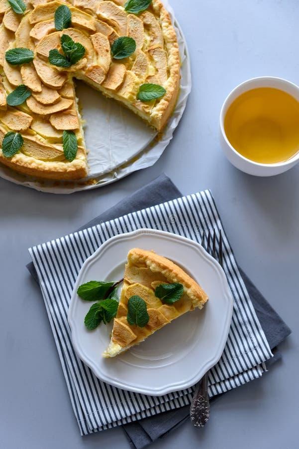 Den hemlagade äppelpajen med ost dekorerade mintkaramellsidor på grå träbakgrund Teatime eller vegetariskt matbegrepp selektivt fotografering för bildbyråer