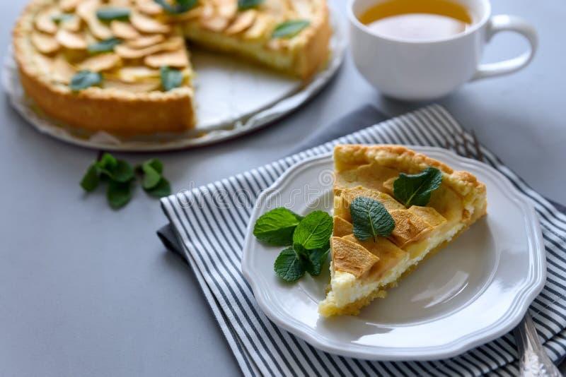 Den hemlagade äppelpajen med ost dekorerade mintkaramellsidor på grå träbakgrund Teatime eller vegetariskt matbegrepp selektivt royaltyfria foton