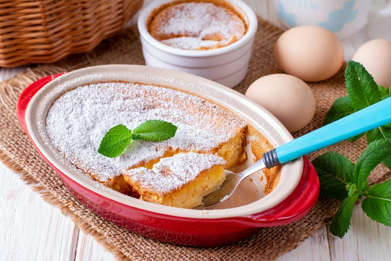 Den hemlagade eldfasta formen, pudding, ostkaka, syrligt, pajen eller mousse i oval stekhet maträtt står på trätabellen med pudra royaltyfria bilder