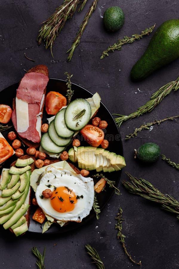 Den hemlagade frukosten, det förvanskade ägget med tomaten skivade arkivbild