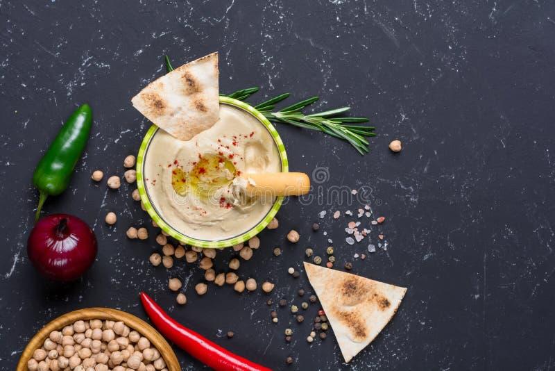 Den hemlagade hummusen med pitabröd- och grissinibrödpinnar, chili, jalapeno på svart stenar tabellen Mellersta - östligt traditi arkivbild