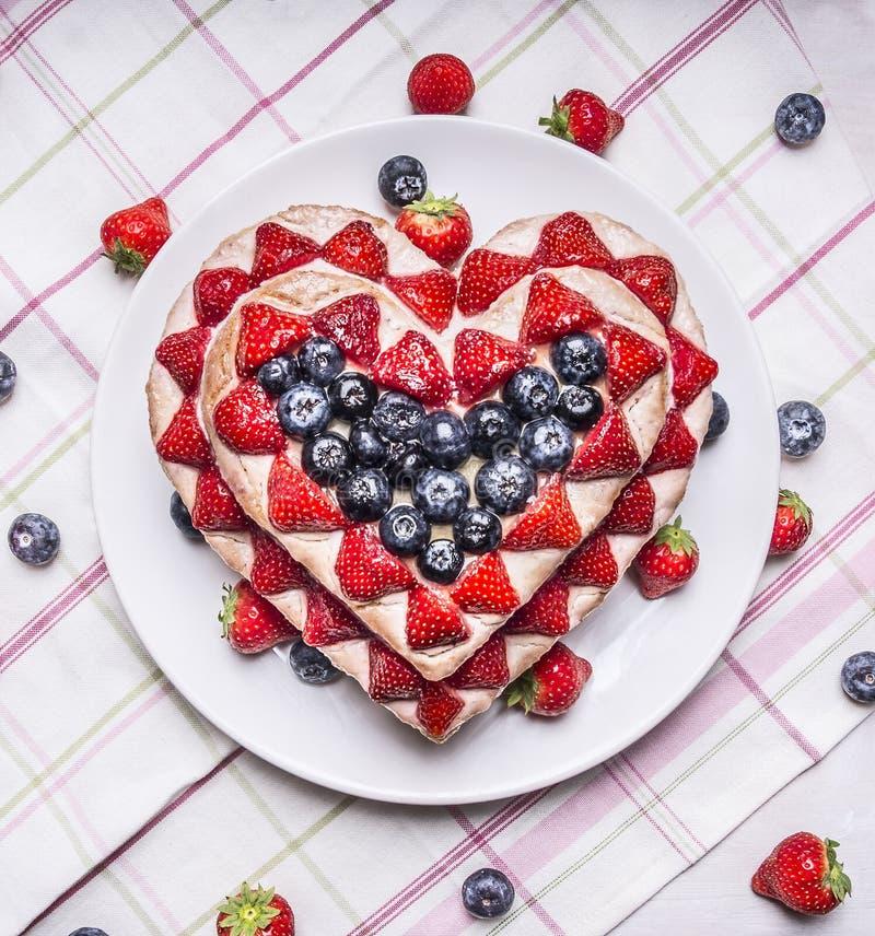 Den hemlagade kakan med jordgubbar och blåbär för valentins daghjärta formade på en vit platta på en randig bordduk med avskummar arkivfoton
