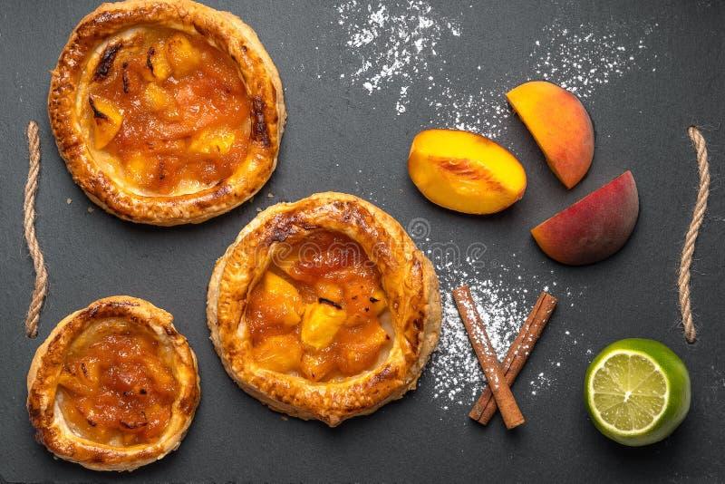 Den hemlagade rundan pusta med persikor på en mörk bakgrund, bredvid persikaskivor, kanelbruna pinnar, limefrukt, pudrat socker b arkivfoto