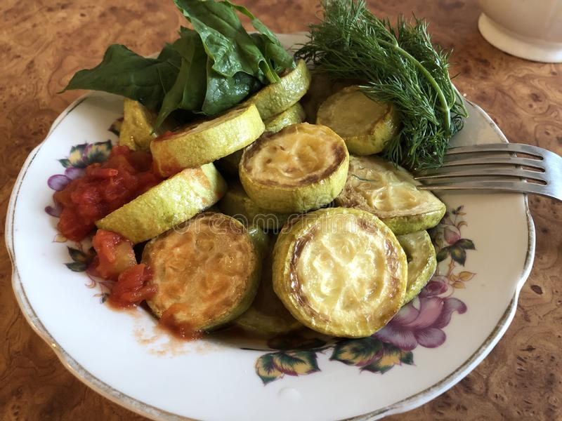 Den hemlagade zucchinin lät småkoka grönsaker med örter på en vit platta royaltyfria bilder