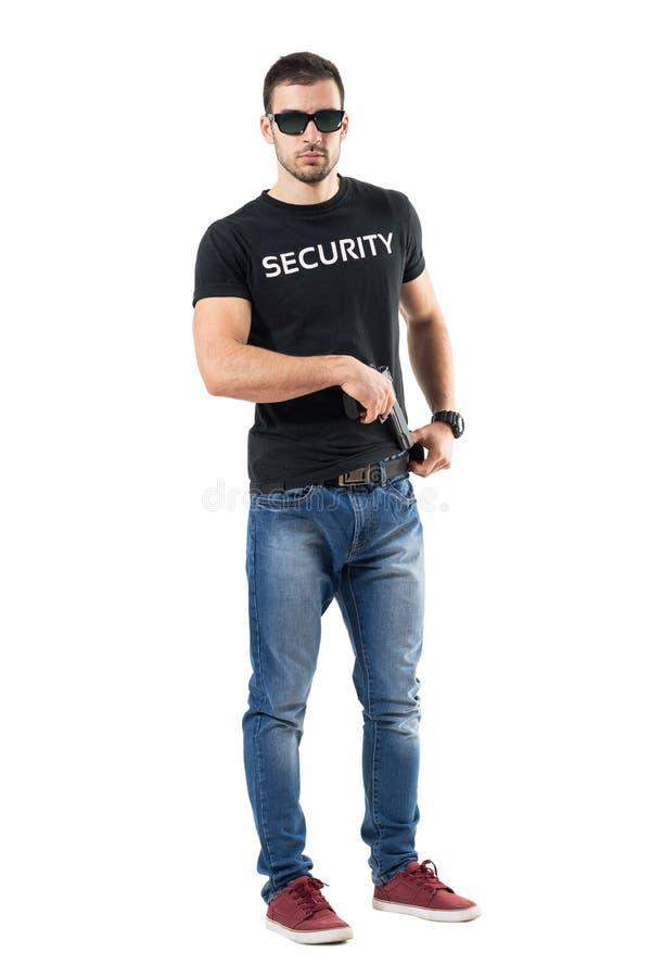 Den hemliga polisen man att ta handeldvapnet från bältet som ser kameran arkivfoton