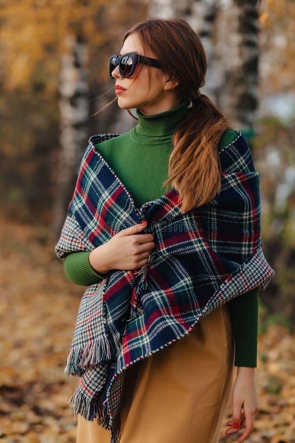 Den hemtrevliga stilfulla unga flickan går på den färgrika hösten parkerar i solglasögon arkivfoton