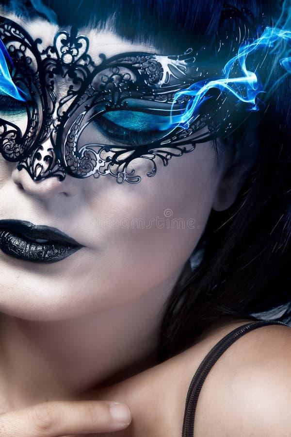 Den Hieratic och härliga kvinnan med Venetian maskerar, blått röker comi arkivfoton