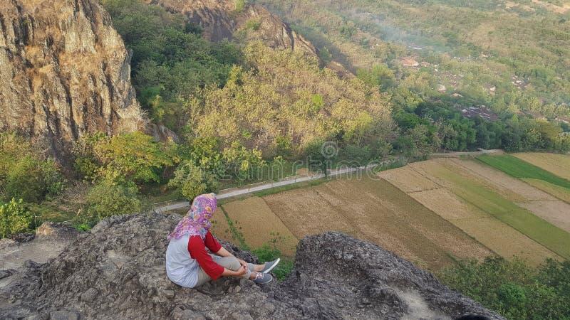 Den Hijab flickan som placerar på maximum av, vaggar berget royaltyfria bilder