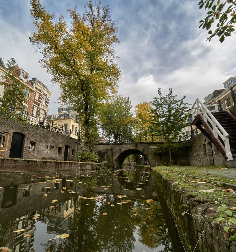 Den historiska kanalen i staden Utrechts centrum i Nederländerna under fallet med blad som täcker marken arkivfoto