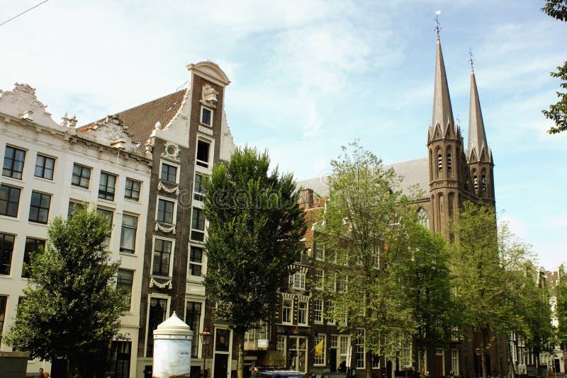 Den historiska kyrkan och husen i den gamla staden av Amsterdam ( royaltyfri bild