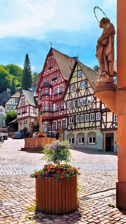 Den historiska marknadsfyrkanten med statyn och halva timrade byggnader i Miltenberg, Bayern, Tyskland royaltyfri foto