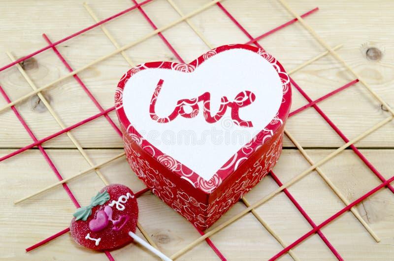Den hjärta formade asken dekorerade med en röd godis arkivfoto