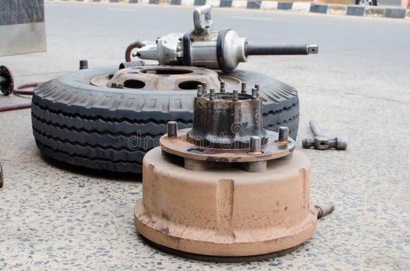 Den hjulnavet och lastbilen tröttar i process av muttern för det ändrande hjulet fotografering för bildbyråer