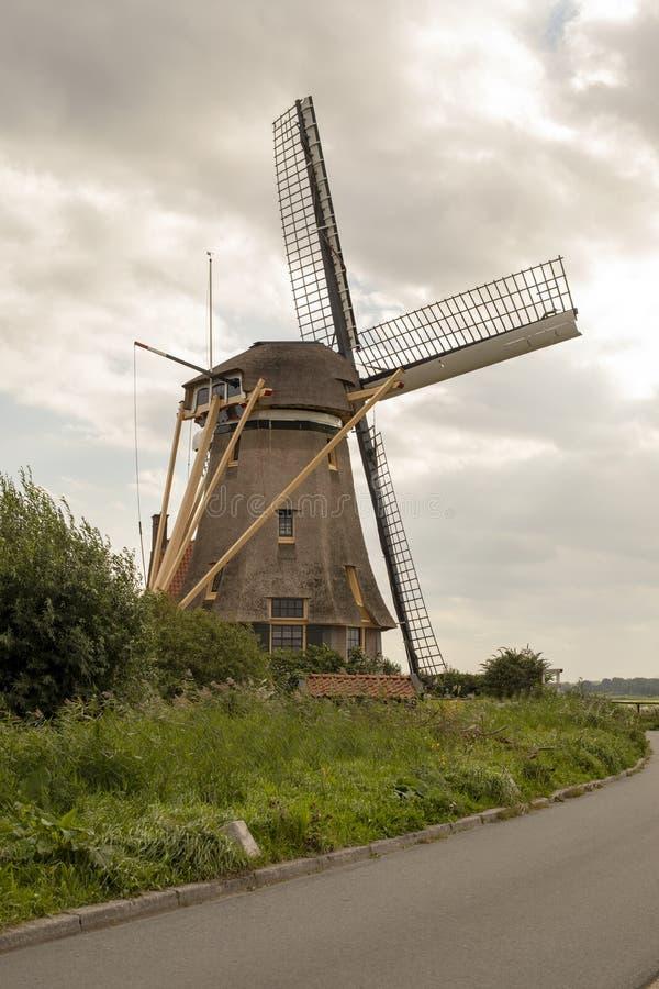 Den holländska väderkvarnen med jättelikt maler blad runt om hörnet av vägen royaltyfria foton
