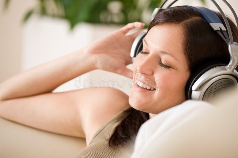 den home hörlurar lyssnar musik som ler till kvinnan arkivbild