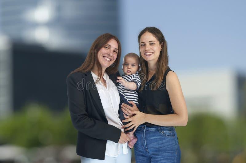 Den homosexuella familjen, unga lesbiska mödrar med deras behandla som ett barn Lesbisk förälskelse arkivfoton